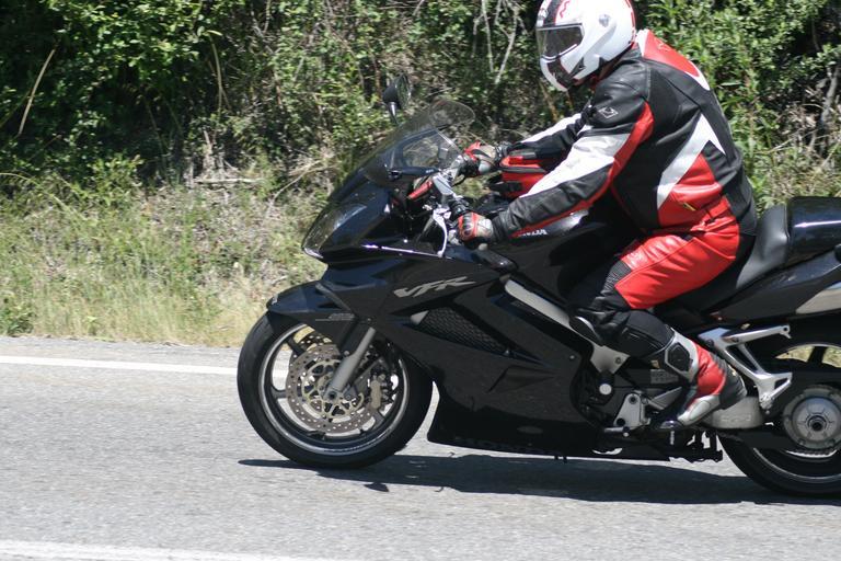 Motorkár jazdí v kompletnom overali, čierna motorka