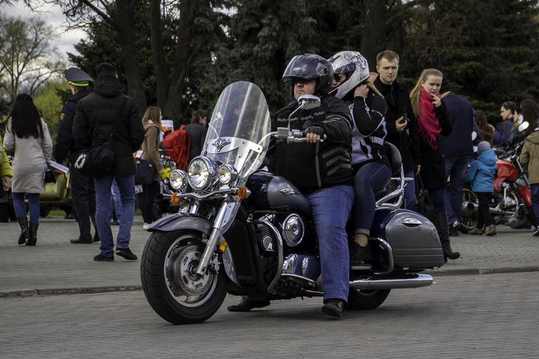 Muž so ženou sedia na motorke, motorkári